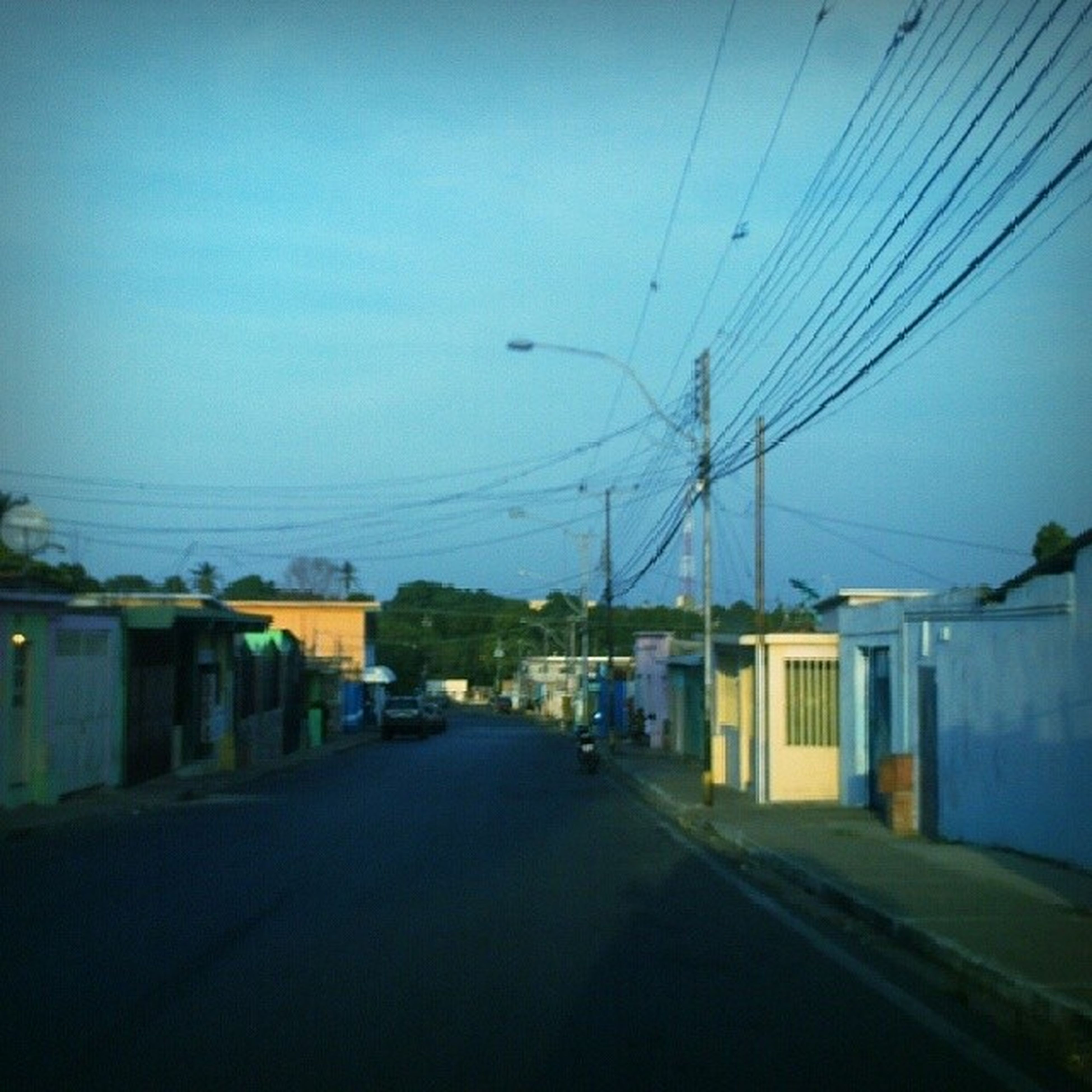 the way forward, building exterior, built structure, architecture, power line, road, electricity pylon, street, transportation, diminishing perspective, electricity, house, clear sky, street light, vanishing point, sky, cable, residential structure, empty, long