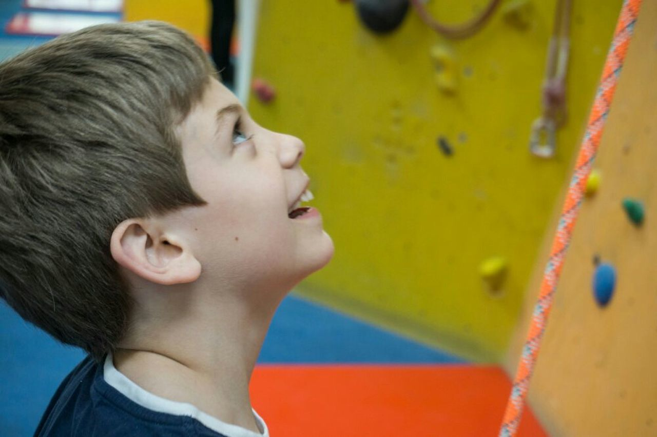 childhood, child, headshot, boys, education, children only, profile view, elementary age, one person, happiness, close-up, cheerful, side view, one boy only, smiling, student, day, real people, multi colored, males, people, outdoors, climbing wall