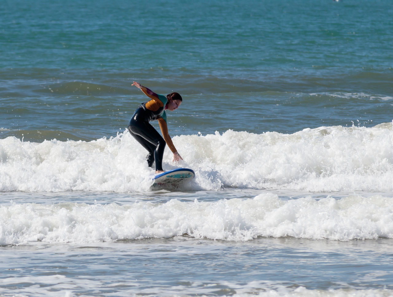 Acre, Israel - March 04, 2017 : Girl in a color waterproof suit exercising in surfing on the board in the Mediterranean sea in Acre beach, Israel Acco Acre Action Active Adventure Beach Beautiful Board Exercise Extreme Girl Holiday Israel Learn Outdoors People Sea Sport Surfing Swim Travel Vacation Water Wave Woman