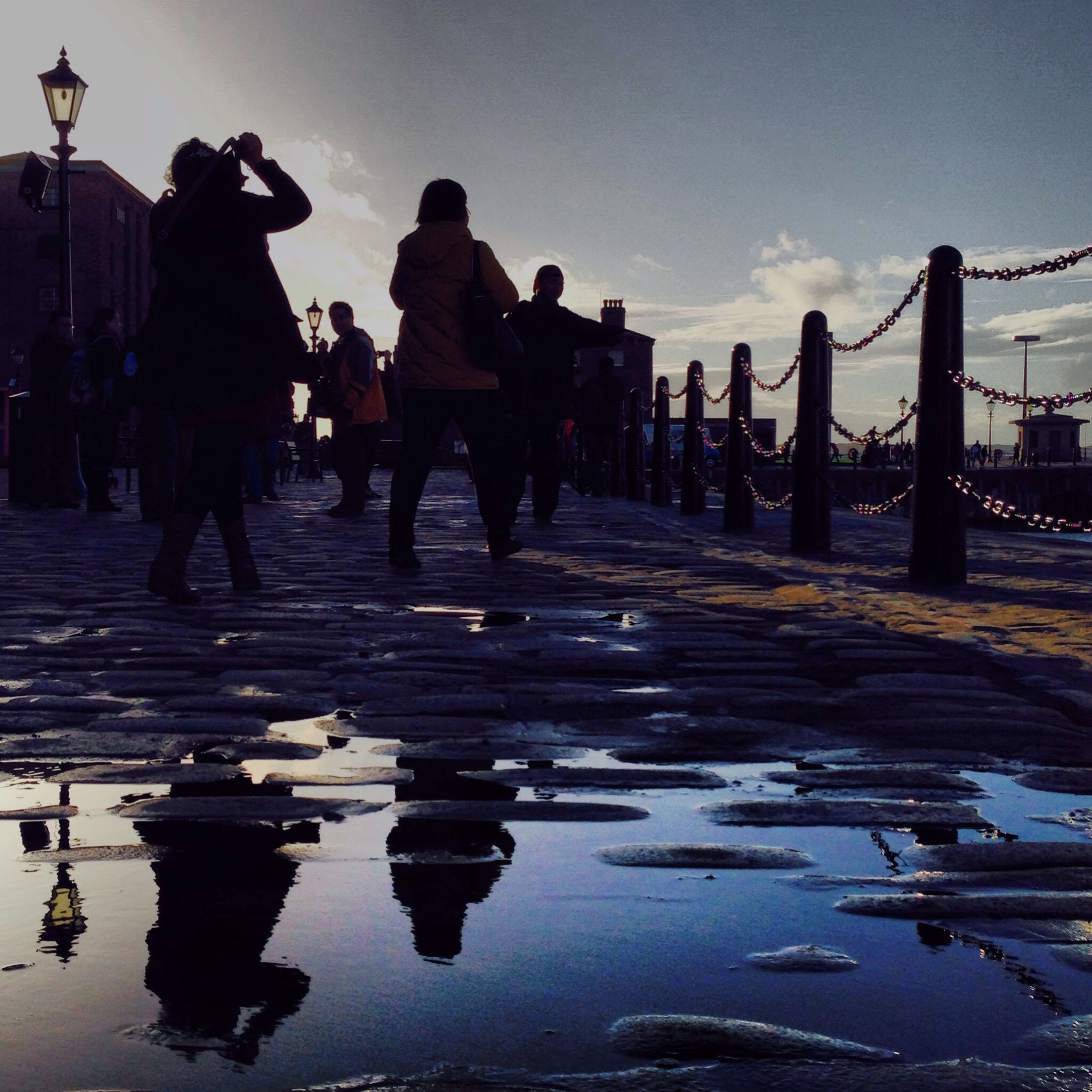 water, sky, reflection, men, large group of people, lifestyles, walking, person, built structure, silhouette, leisure activity, incidental people, architecture, sea, wet, beach, medium group of people, building exterior, waterfront