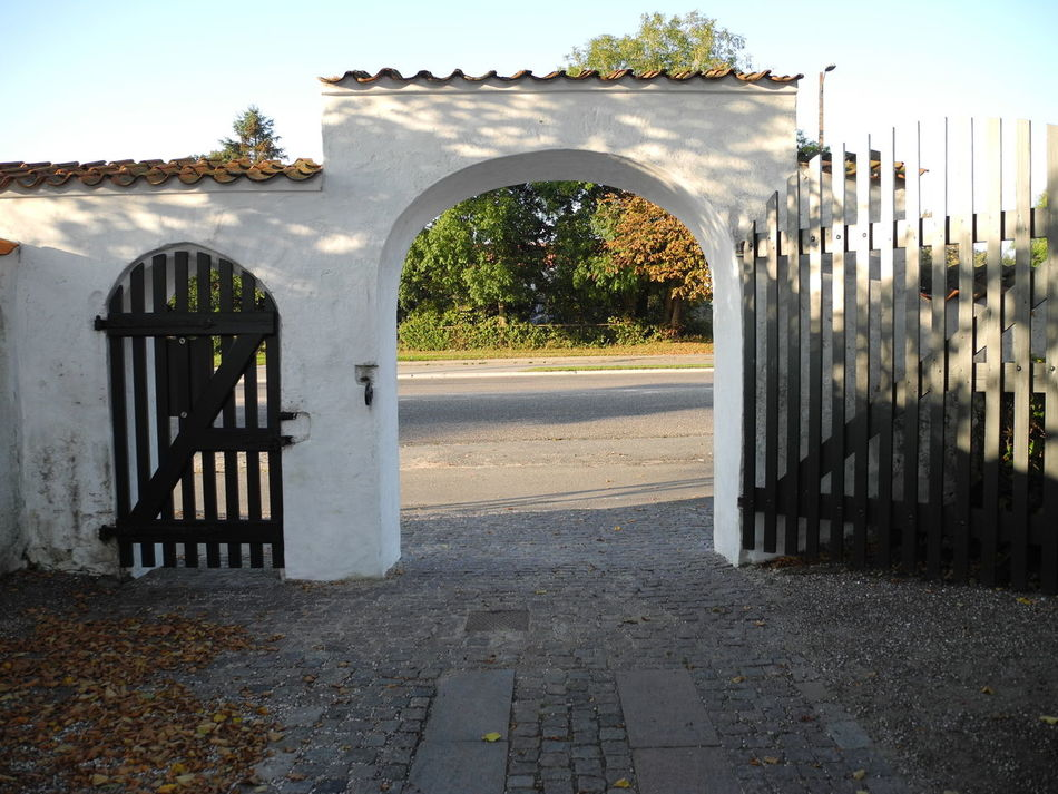 View through the gate of Storemagleby Church to Kirkevej (Church Road) in early autumn (fall) - Built Structure Arch Architecture Gate Tree Entrance Outdoors Tranquil Scene Day Building Exterior Plant Tranquility Scenics Growth Nature - in the small village of Store Magleby on the island of Amager in Denmark