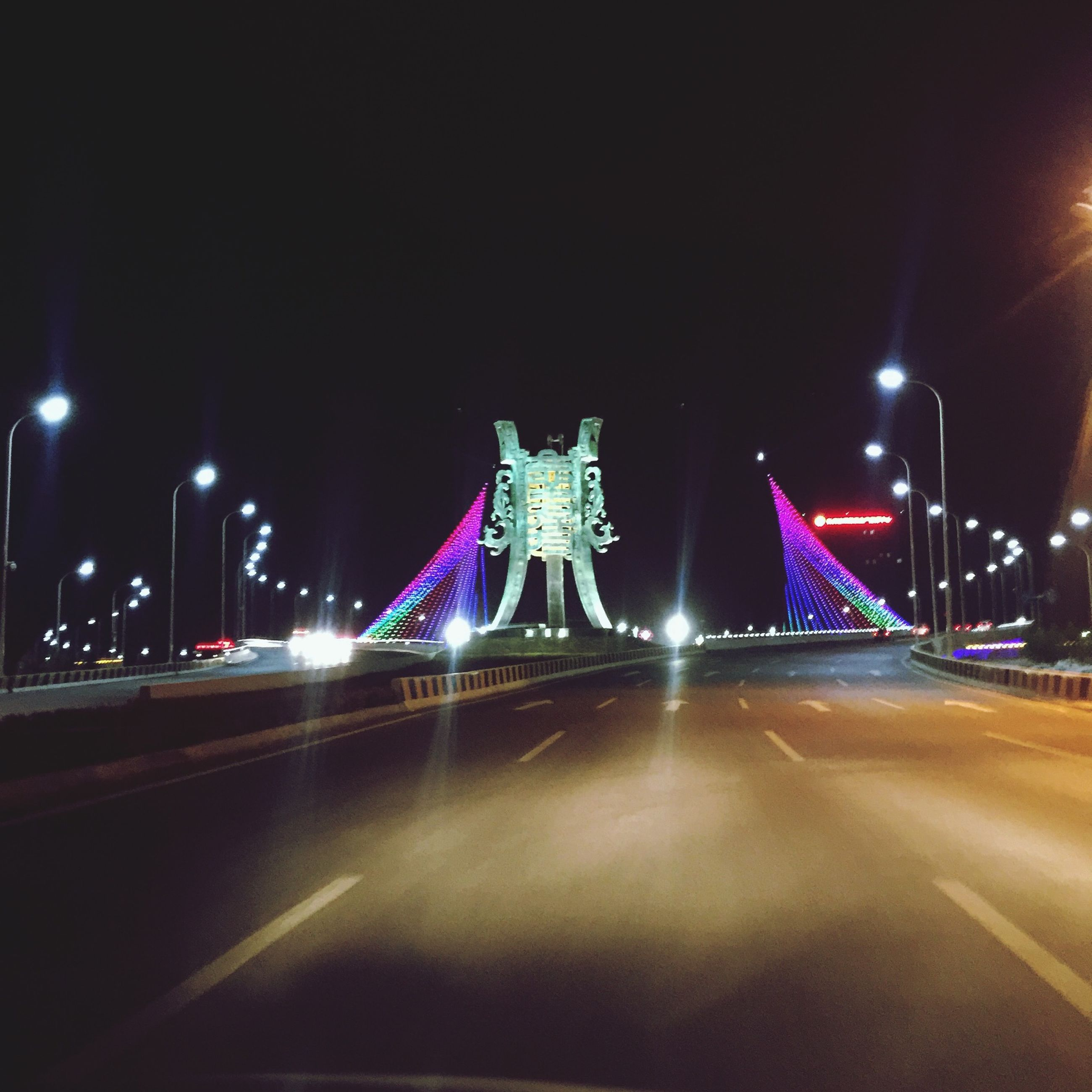 illuminated, night, transportation, the way forward, road, street light, copy space, clear sky, built structure, architecture, lighting equipment, street, road marking, city, long exposure, light trail, diminishing perspective, building exterior, bridge - man made structure, vanishing point