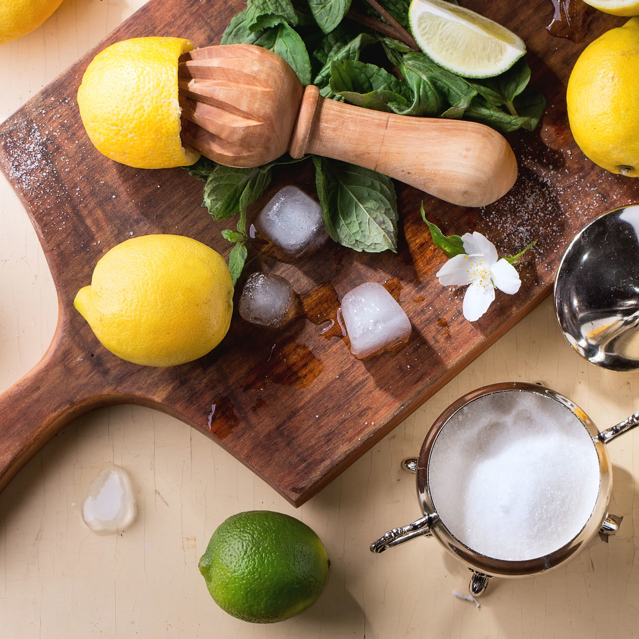 Heap of whole and sliced lemons, limes and mint with citrus reamer and ice cubes on wooden cutting board over wooden background. Rustic sun light. Top view. Assortment Bright Citrus Fruit Cutting Board Food Food And Drink Fresh Fruits Ice Cubes Ingredients Jasmine Flower Lemon Lemonade Lime Mint Refreshment Sliced Sugar Summer Top View Variety Vitamin Whole Wooden Background Yellow