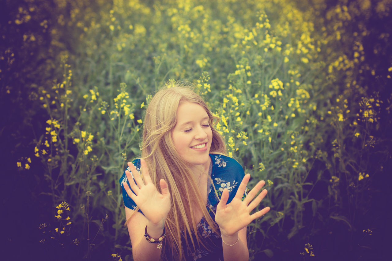 Beautiful Woman Beauty Blond Hair Canola Day Field Flower Front View Happiness Leisure Activity Lifestyles Long Hair Nature One Person Outdoors People Portrait Real People Smiling Standing Summer Young Adult Young Women