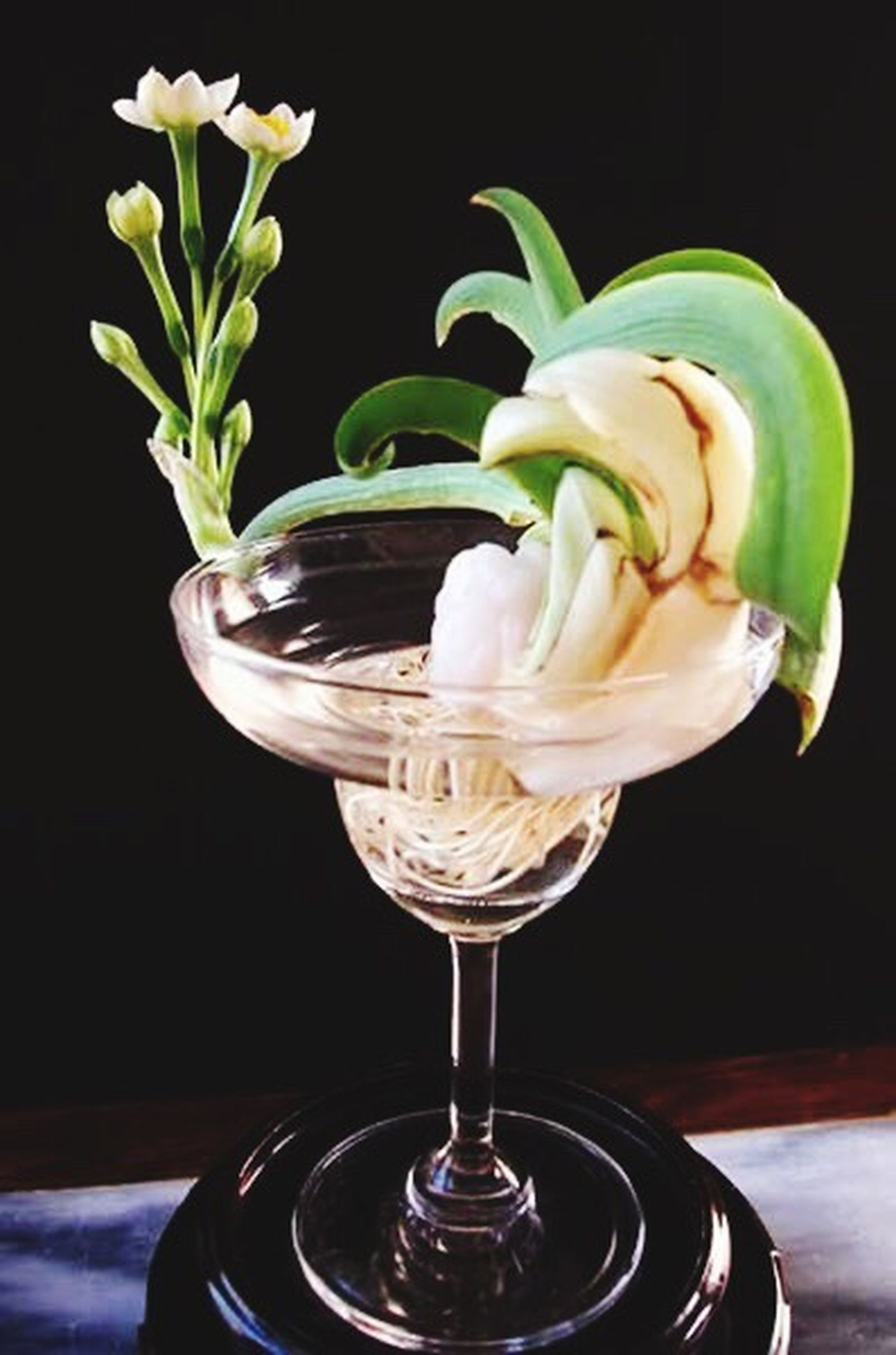 freshness, drink, table, refreshment, flower, drinking glass, indoors, close-up, food and drink, fragility, still life, glass - material, wineglass, vase, petal, water, glass, focus on foreground, transparent, studio shot