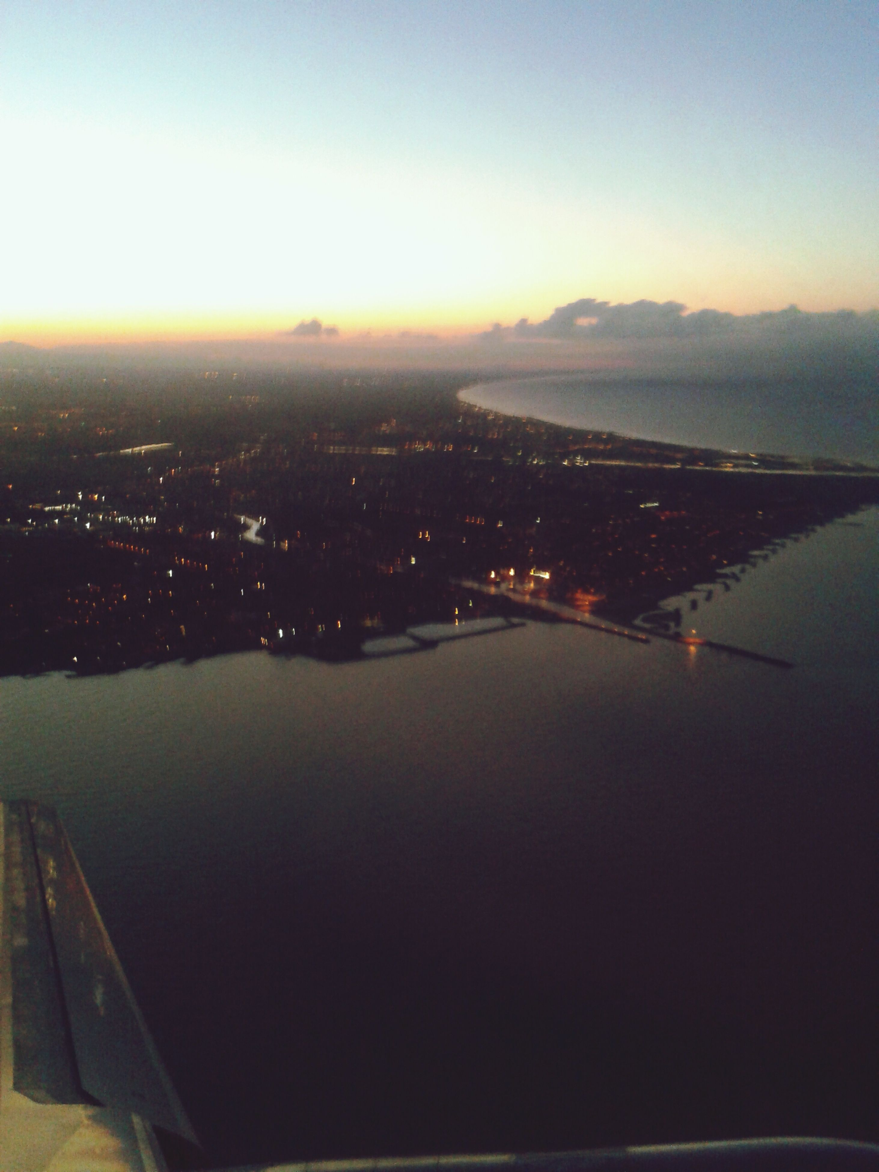 airplane, aerial view, air vehicle, transportation, sunset, sky, aircraft wing, mode of transport, landscape, cityscape, flying, part of, city, cropped, clear sky, scenics, built structure, copy space, architecture, high angle view