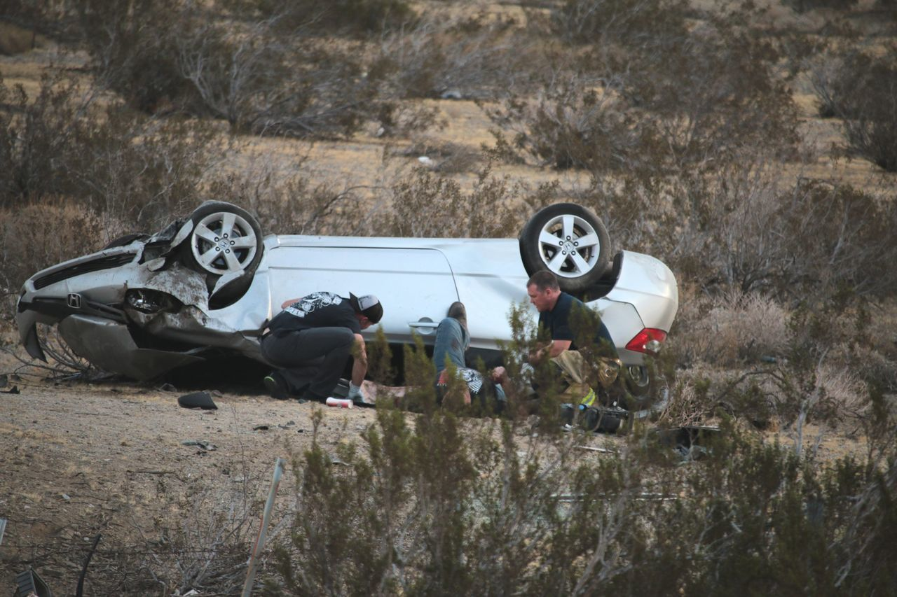 An injured man being helped by a volunteer firefighter and a passing motorist after a rollover crash on 29 Palms Highway (route 62) Accident Car Coachella Valley Crash Field Good Samaritans Injured Outdoors Riverside County Single Car Volunteer Firefighters
