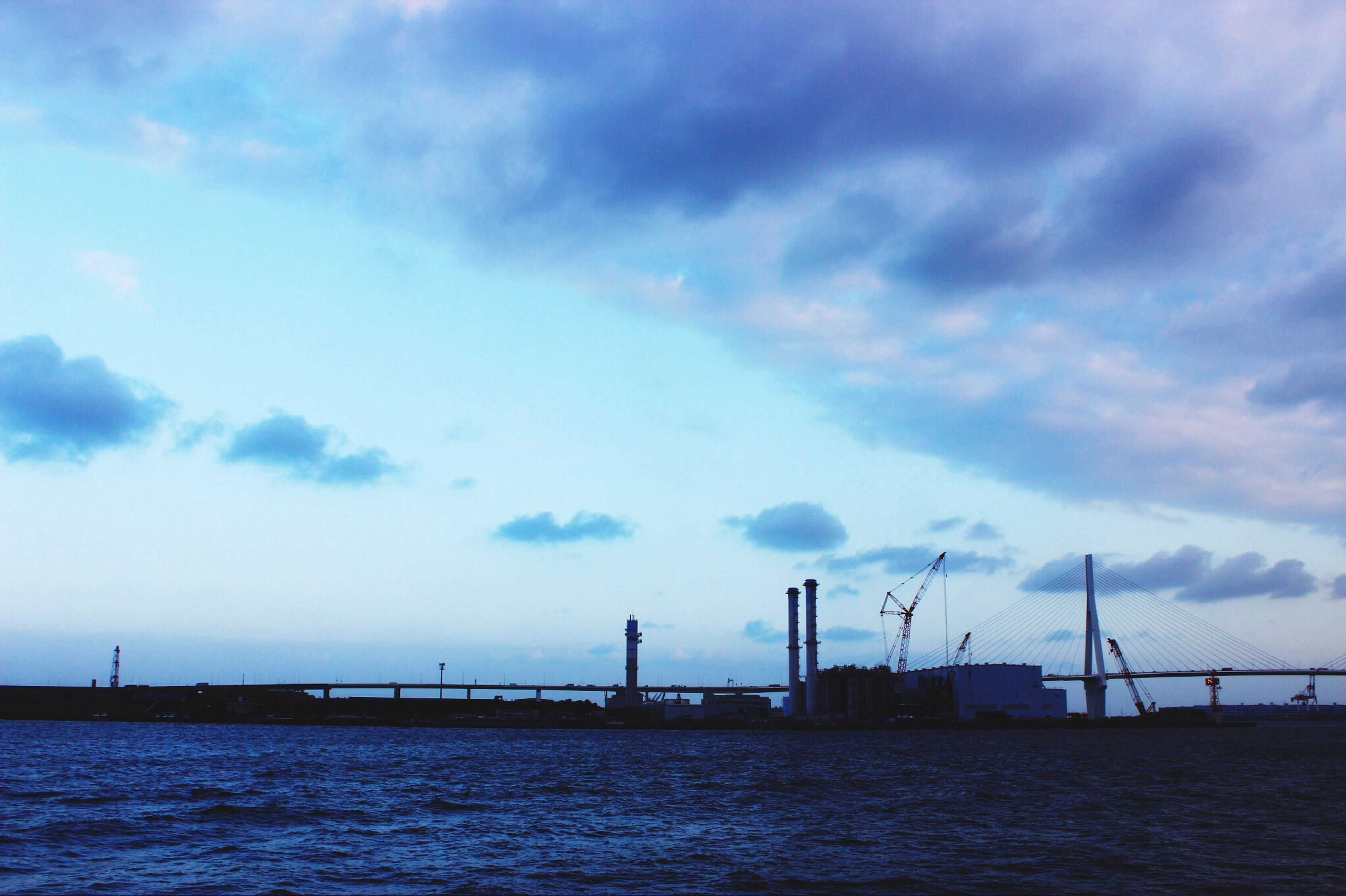 water, sky, waterfront, sea, cloud - sky, built structure, connection, cloudy, architecture, cloud, river, nature, rippled, tranquility, tranquil scene, outdoors, dusk, scenics, no people, bridge - man made structure