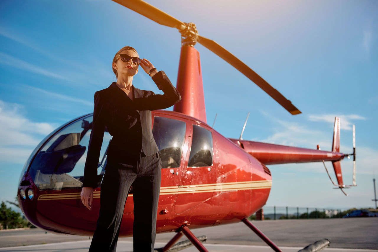 Business woman near the helicopter. Business, success and luxury concept Aircraft Airplane Airport Ambitious Businesswoman Career Females Helicopter Landing Field Lifestyles Luxury Mode Of Transport One Person Outdoors People Private Plane Rich Sky Standing Success Successful Sunny Day Transportation Young Adult Young Women