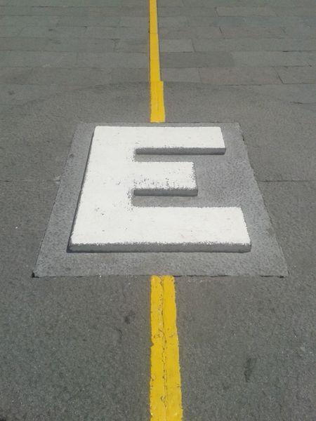 Asphalt Communication Day Equator Equator Line Letter E No People Outdoors Road Road Sign Symbol Yellow e