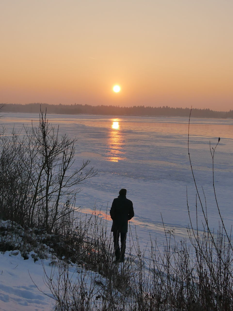 sunset, nature, beauty in nature, silhouette, water, sun, real people, tranquil scene, tranquility, scenics, one person, winter, reflection, sky, leisure activity, cold temperature, rear view, sunlight, outdoors, standing, full length, lake, snow, men, lifestyles, day, people