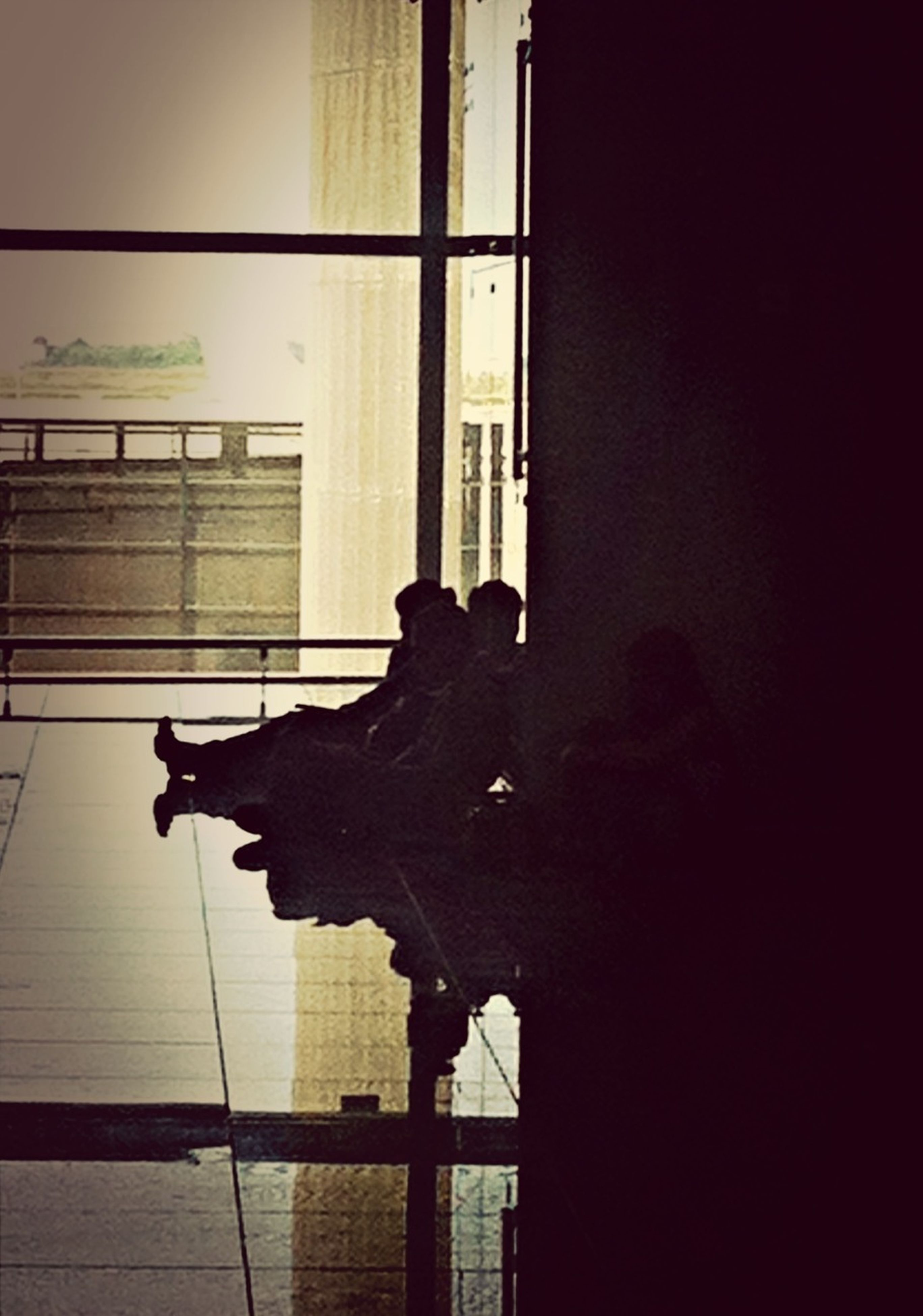 indoors, window, silhouette, architecture, built structure, full length, low angle view, wall - building feature, building exterior, shadow, glass - material, side view, home interior, sunlight, building, standing, day, human representation