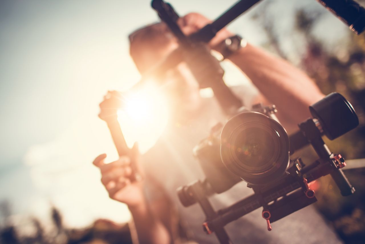 Video Gimbal Operator. Video Making. DSLR Camera on a Gimbal Equipment. Adult Arts Culture And Entertainment Close-up Day Gimbal Human Body Part Human Hand Lens Flare Men Motion Picture Music One Person Outdoors People Real People Video Making Videomaker Youth Culture