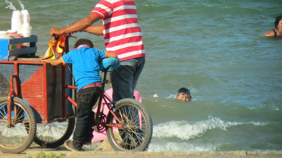 Two People Outdoors Water Leisure Activity Cycling Togetherness Men Vacations Real People Adult Day People Adults Only Low Section Child Work Child Worker Helping Beach Coast Job Slpash
