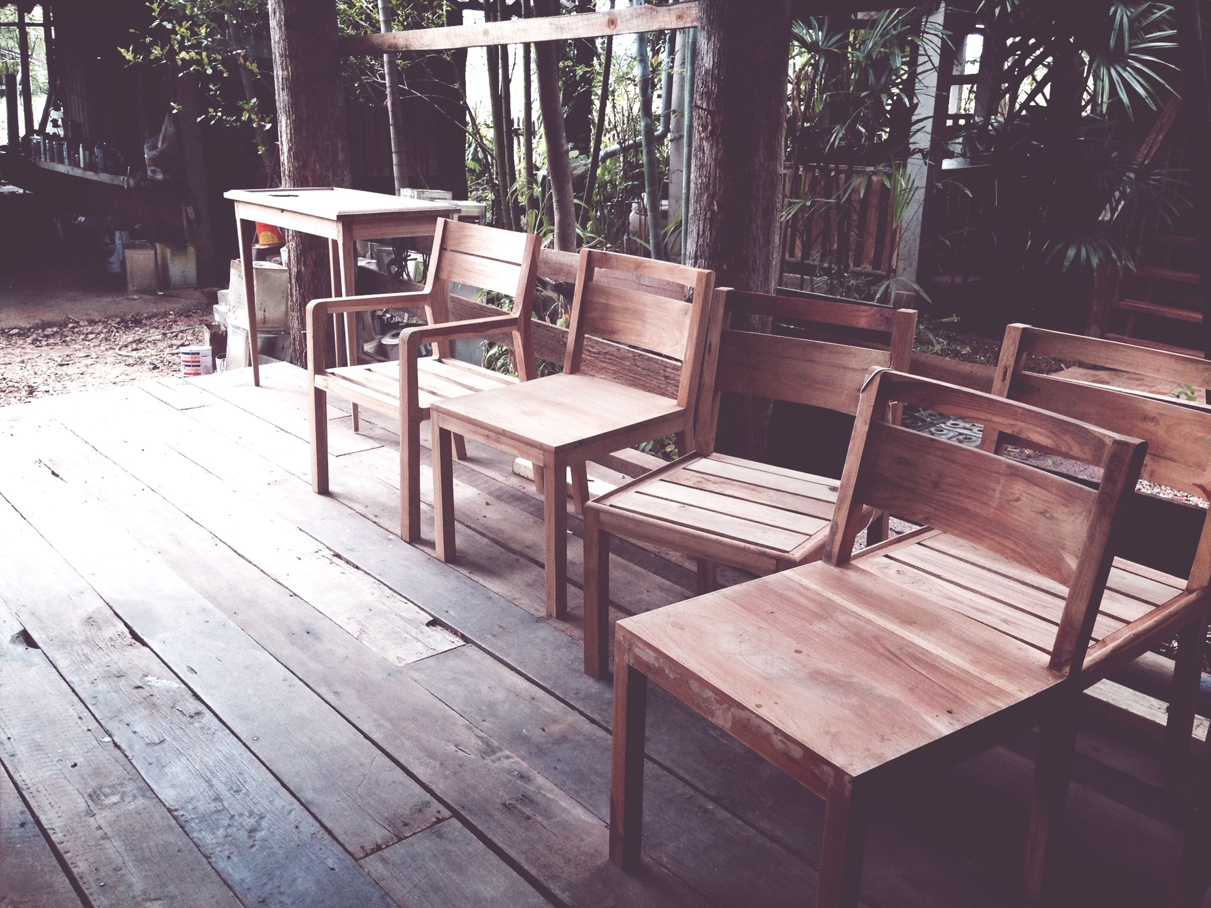 chair, empty, absence, bench, wood - material, seat, table, tree, sunlight, furniture, relaxation, shadow, wooden, wood, day, built structure, park bench, no people, outdoors, high angle view