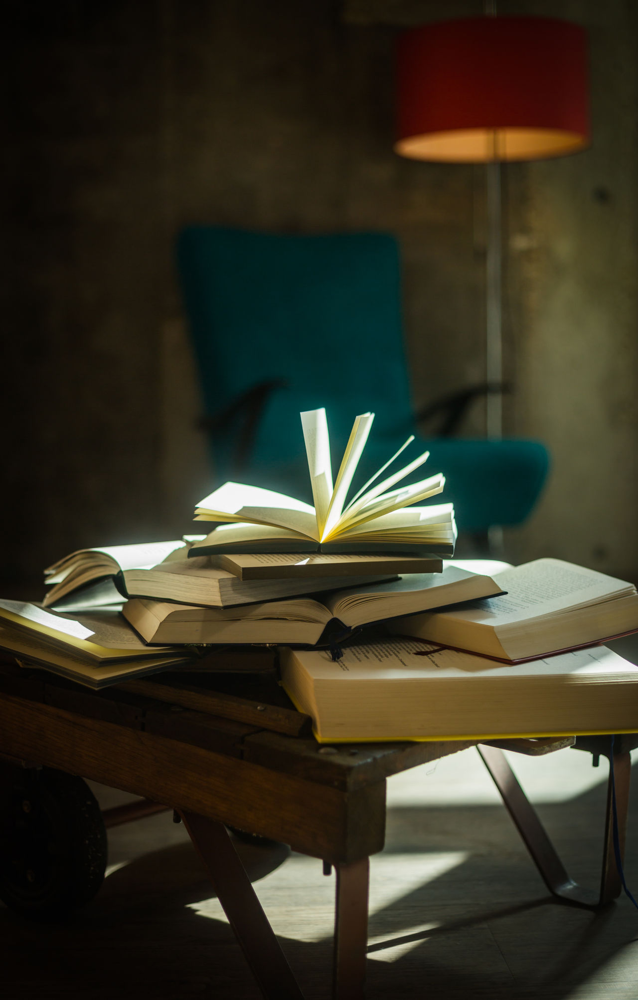 A pile of open books, bathed in light with a lamp and a chair in the backround, waiting for the reader to return No People Indoors  Illuminated Table Books BookLovers Light Books ♥ Book Reading A Book Nobody