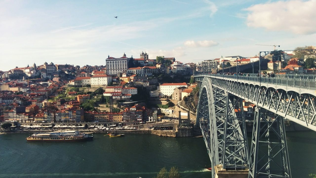 architecture, built structure, bridge - man made structure, connection, river, city, sky, building exterior, transportation, water, outdoors, cityscape, day, no people, chain bridge