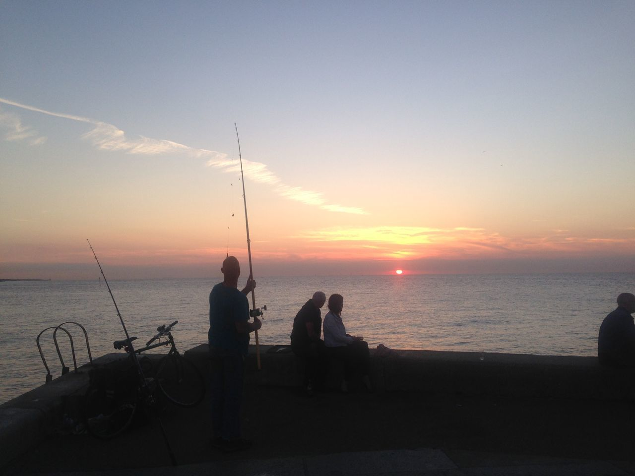 sea, sunset, silhouette, horizon over water, water, scenics, tranquil scene, nature, beauty in nature, sky, tranquility, idyllic, fishing pole, real people, men, leisure activity, fishing, weekend activities, outdoors, standing, beach, togetherness, sitting, people