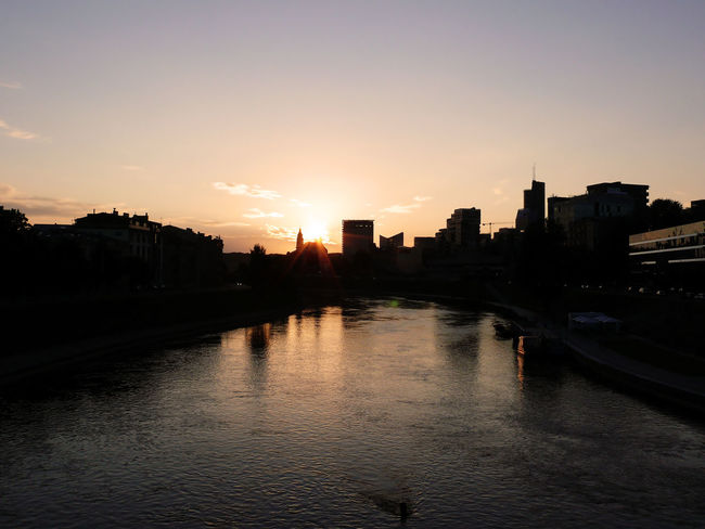 exploring Vilnius' building exterior at sunset || Architecture Beauty In Nature Building Building Exterior Built Structure Canal City City Life Cityscape Nature Neris No People Orange Color Outdoors Rippled River Scenics Sky Skyline Sun Sunset Tranquil Scene Tranquility Urban Skyline Water