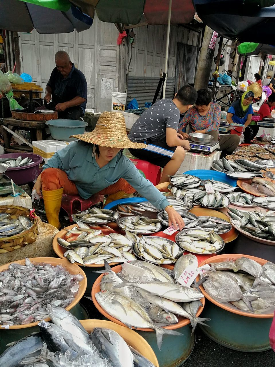 market, market stall, seafood, retail, selling, market vendor, real people, for sale, small business, fish market, men, occupation, food, fish, choice, food and drink, working, large group of objects, freshness, healthy eating, large group of people, women, day, business, outdoors, adult, people