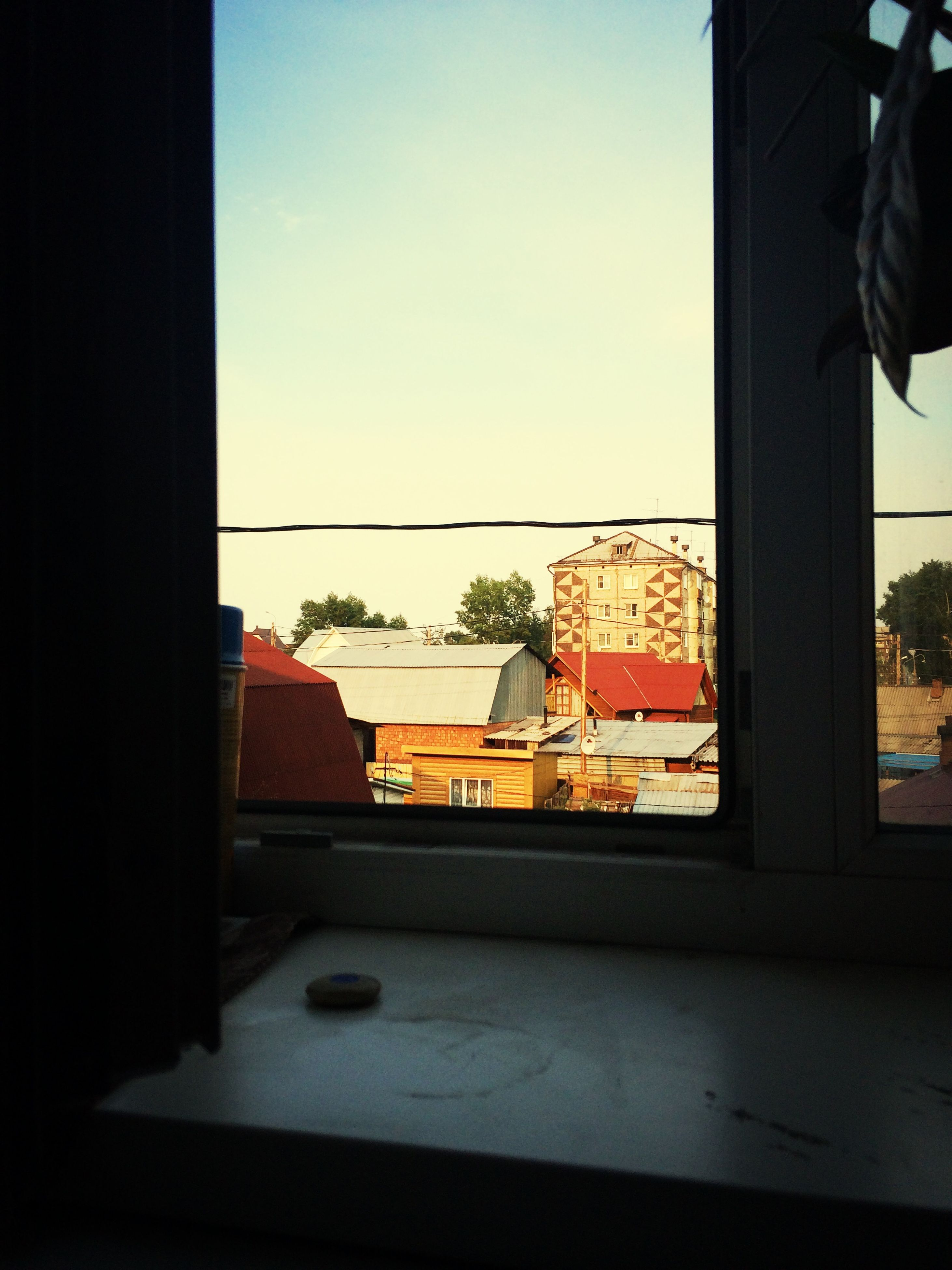 window, architecture, indoors, built structure, building exterior, glass - material, sky, transparent, house, clear sky, sunlight, day, residential structure, home interior, looking through window, sunset, wall - building feature, city, no people, window sill
