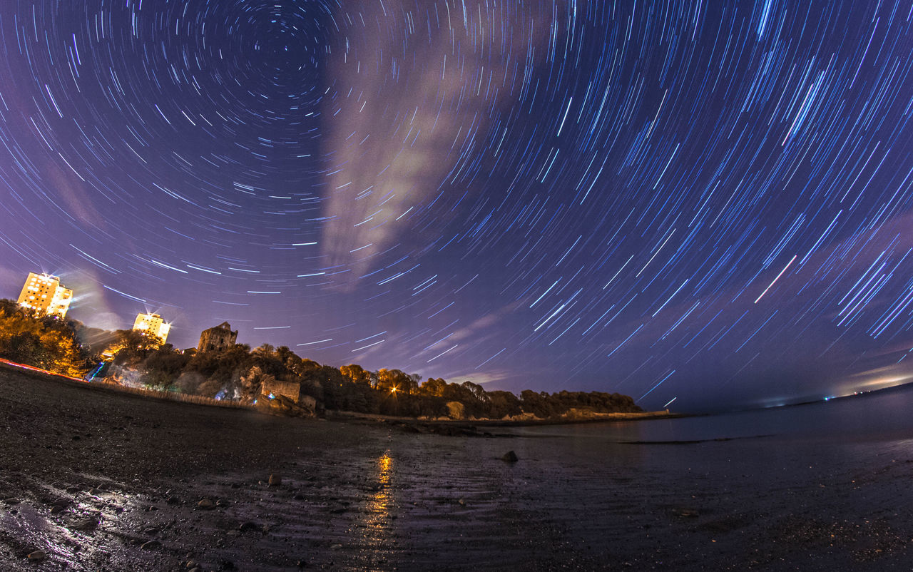 long exposure, night, star trail, scenics, beauty in nature, star - space, nature, water, tranquil scene, sky, motion, tranquility, outdoors, blurred motion, astronomy, no people, sea, illuminated, mountain, galaxy