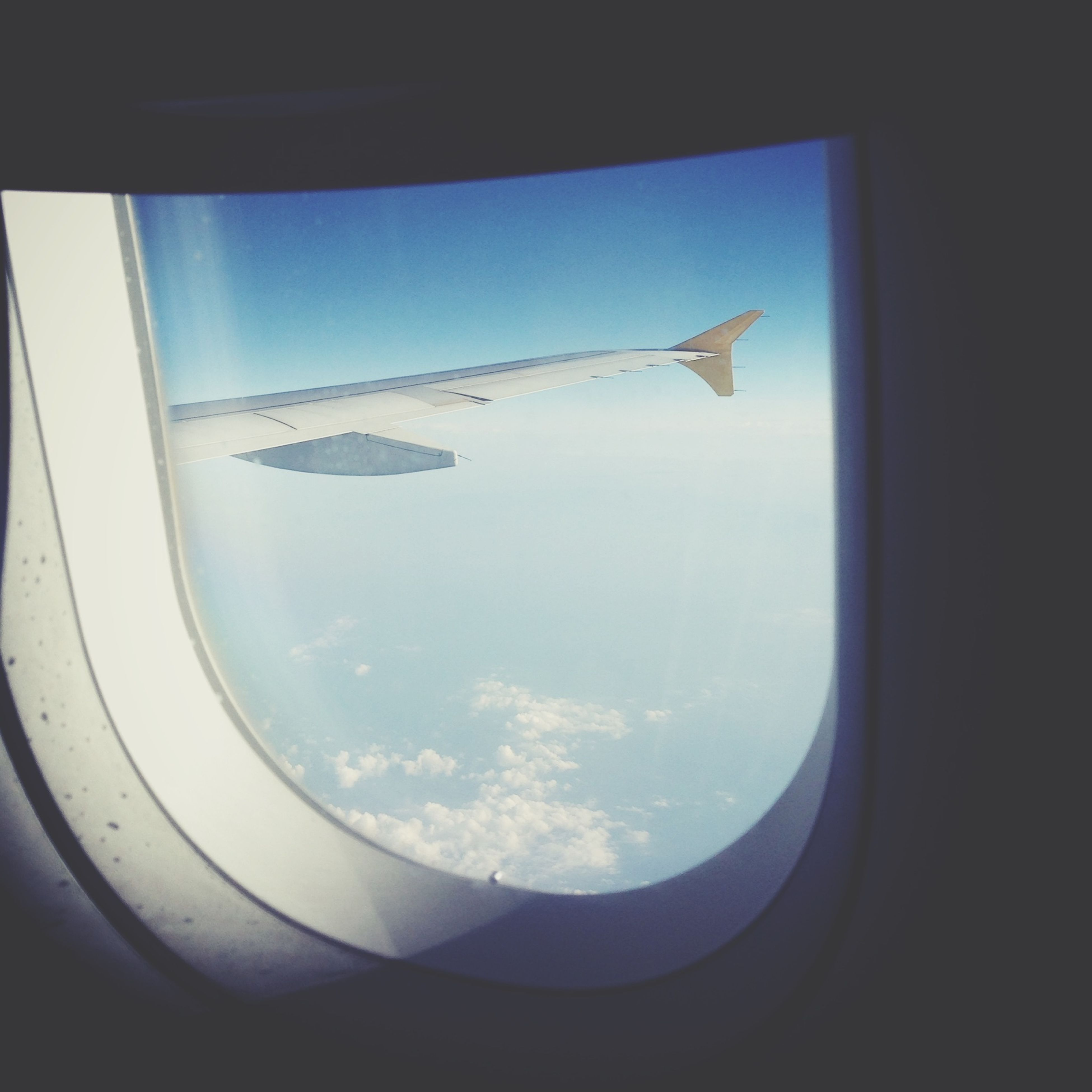 airplane, flying, air vehicle, transportation, window, mode of transport, vehicle interior, aircraft wing, sky, transparent, glass - material, mid-air, part of, journey, indoors, cropped, travel, looking through window, aircraft, public transportation