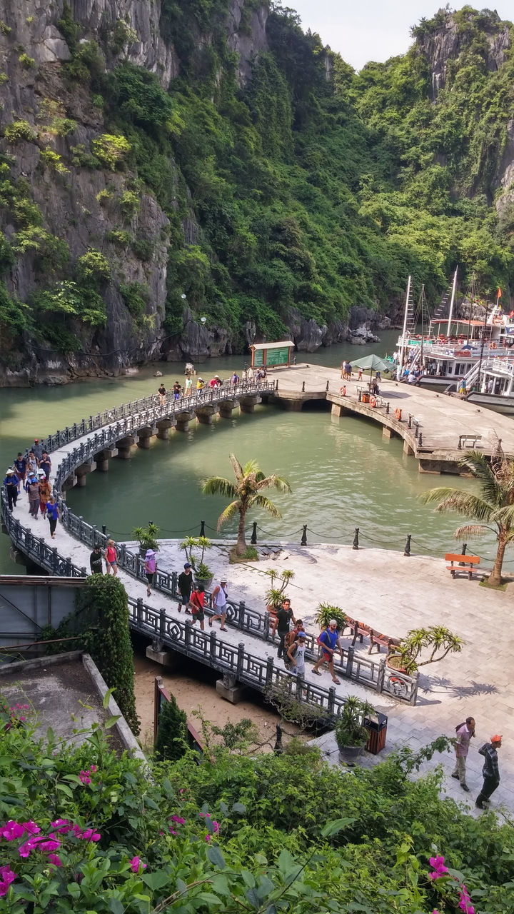 water, tree, nautical vessel, large group of people, transportation, real people, nature, boat, river, day, mode of transport, outdoors, waterfront, growth, high angle view, beauty in nature, built structure, riverbank, bridge - man made structure, lifestyles, moored, plant, scenics, women, architecture, men, mountain, flower, sky, people