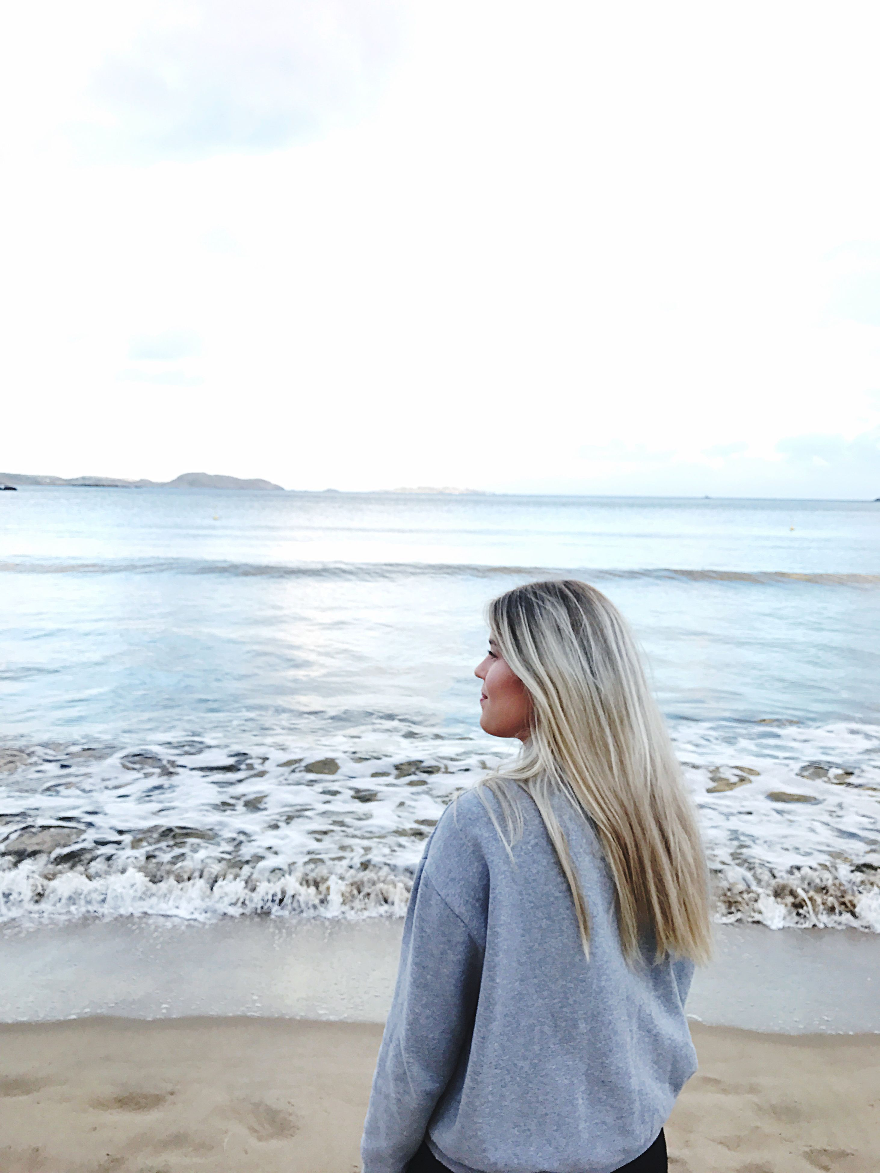 sea, horizon over water, beach, water, one person, sky, nature, blond hair, sand, standing, outdoors, wave, scenics, real people, day, beauty in nature, young adult, people