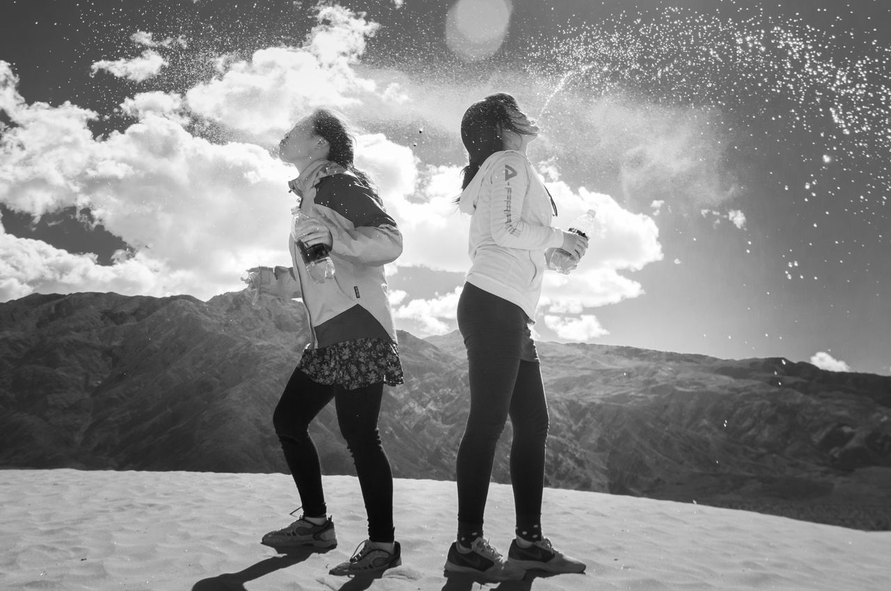 real people, togetherness, mountain, casual clothing, sky, full length, leisure activity, standing, outdoors, two people, friendship, nature, day, happiness, sunlight, lifestyles, cloud - sky, girls, bonding, young women, beauty in nature, young adult, people