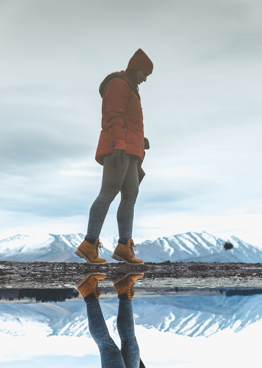 full length, water, one person, standing, reflection, real people, sky, cloud - sky, outdoors, nature, lake, casual clothing, leisure activity, day, lifestyles, tranquil scene, scenics, men, tranquility, beauty in nature, snow, winter, salt - mineral, people