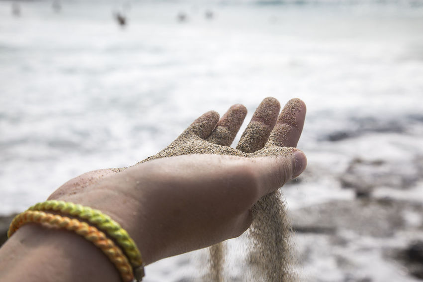 Sand trickle through fingers on beach Grain Of Sand Hawaii Indian Ocean Beach Caribbean Close-up Day Focus On Foreground Human Body Part Human Hand Leisure Activity Lifestyles Nature One Person Outdoors Pacific Ocean People Real People Rippled Shoreline Summer Trickle Water Waves