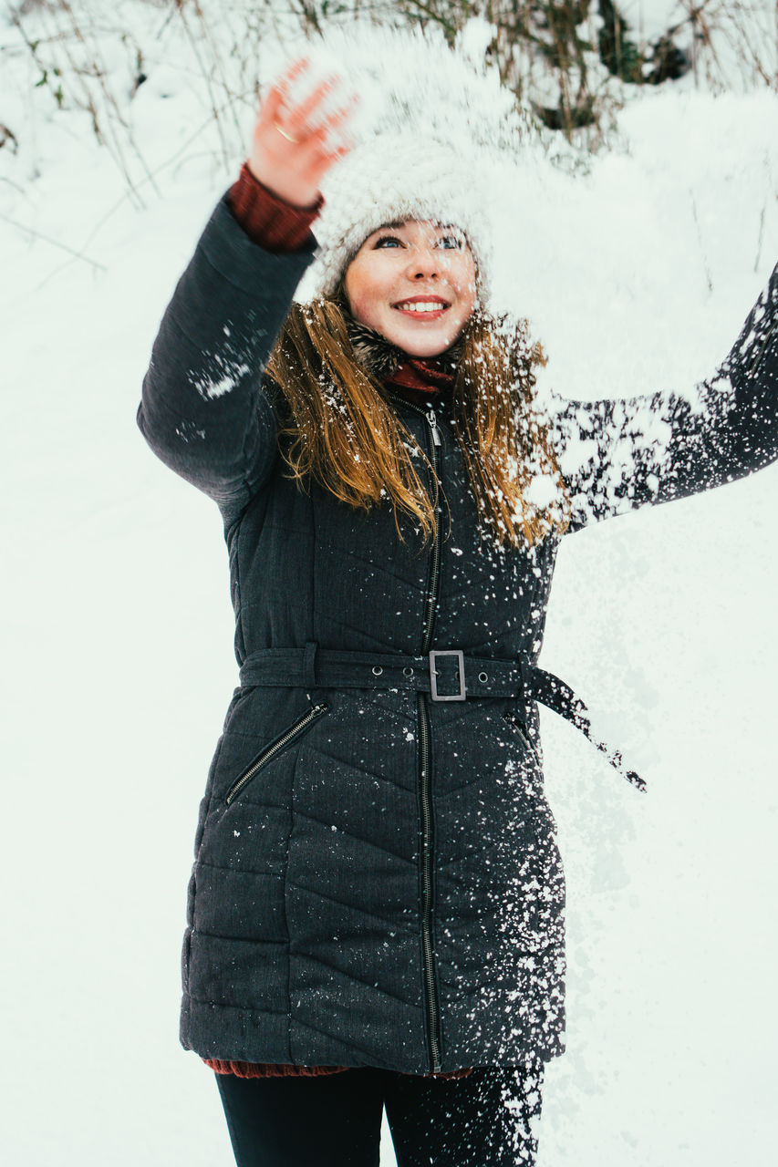 Portrait Of Young Woman Playing In The Snow