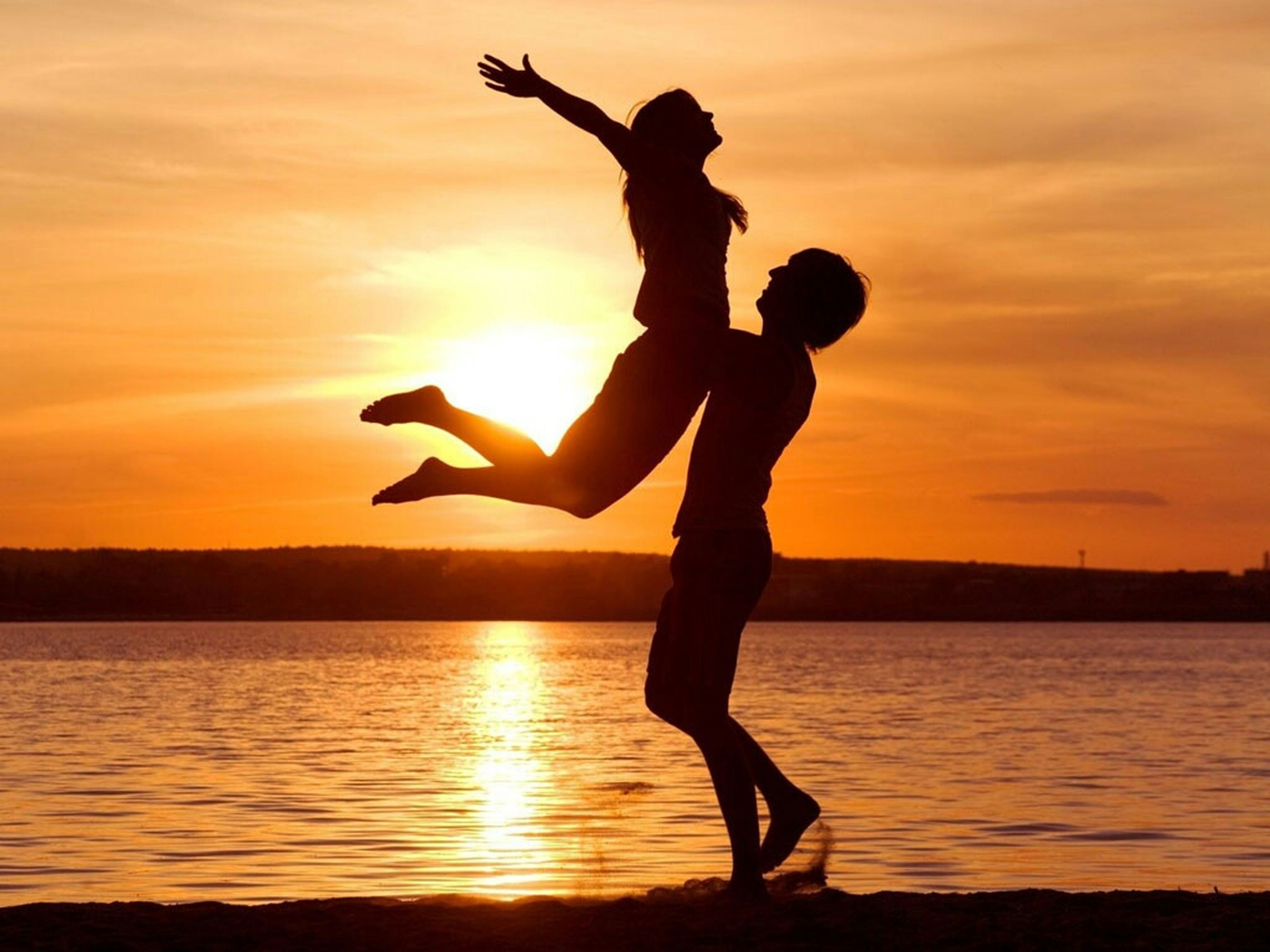 sunset, silhouette, orange color, water, sky, leisure activity, mid-air, sun, sea, lifestyles, jumping, full length, arms raised, scenics, beauty in nature, arms outstretched, nature, enjoyment