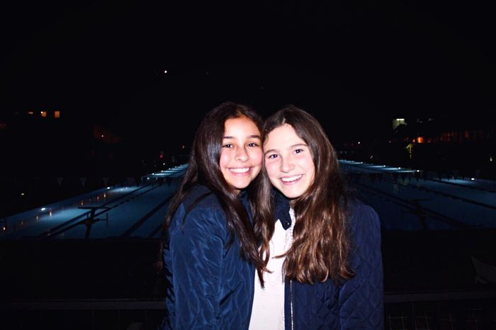 Two People Togetherness Friendship Night Portrait Smiling Only Young Women Brown Hair Happiness People Looking At Camera Fun Adults Only Long Hair Bonding Front View Embracing Outdoors Young Women Enjoyment