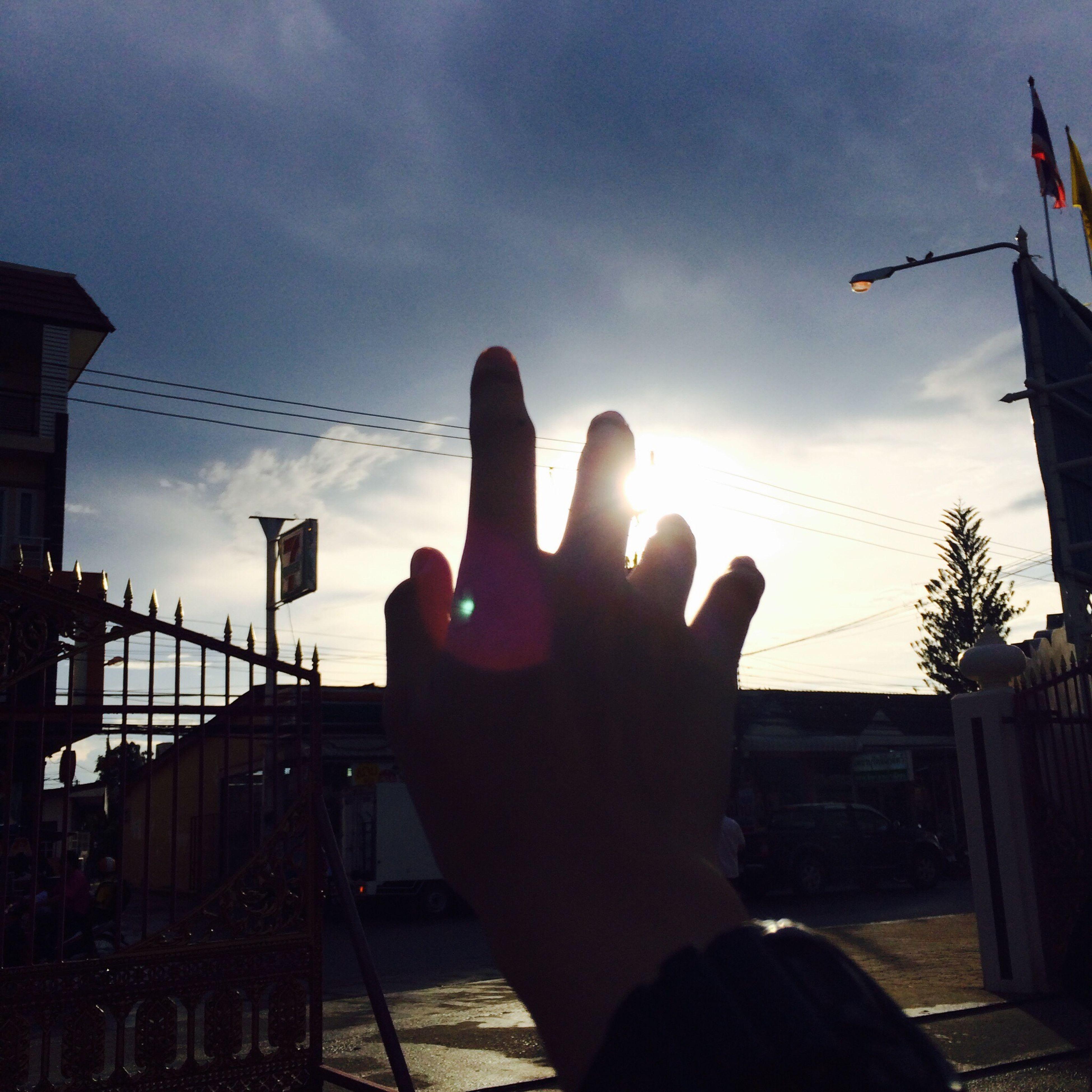 person, sky, part of, silhouette, sunset, cropped, lifestyles, built structure, human finger, building exterior, unrecognizable person, cloud - sky, holding, architecture, cloud, leisure activity, men