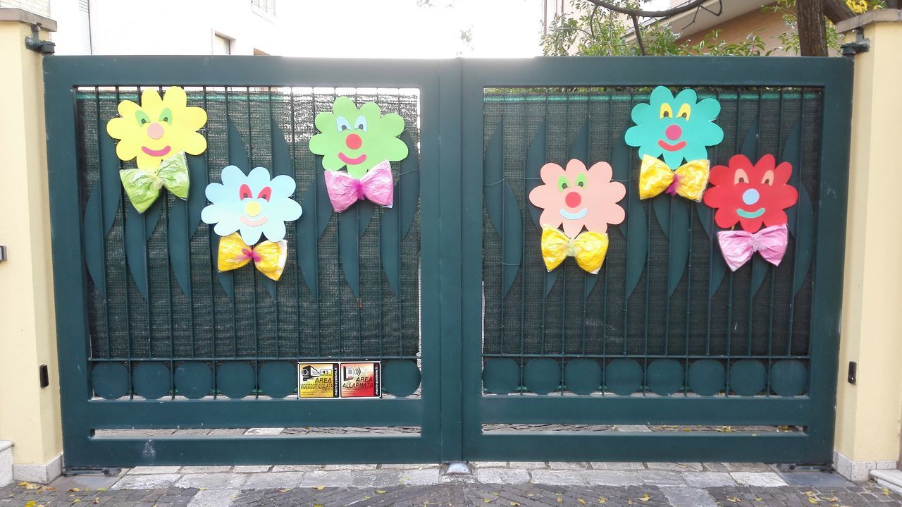 Closed Multi Colored Safety Flower Protection Metal Security Door Close-up Building Exterior Growth Outdoors Day Colorful Multicolored Flower Head Resilenza Clown Resilient fragility Freshness