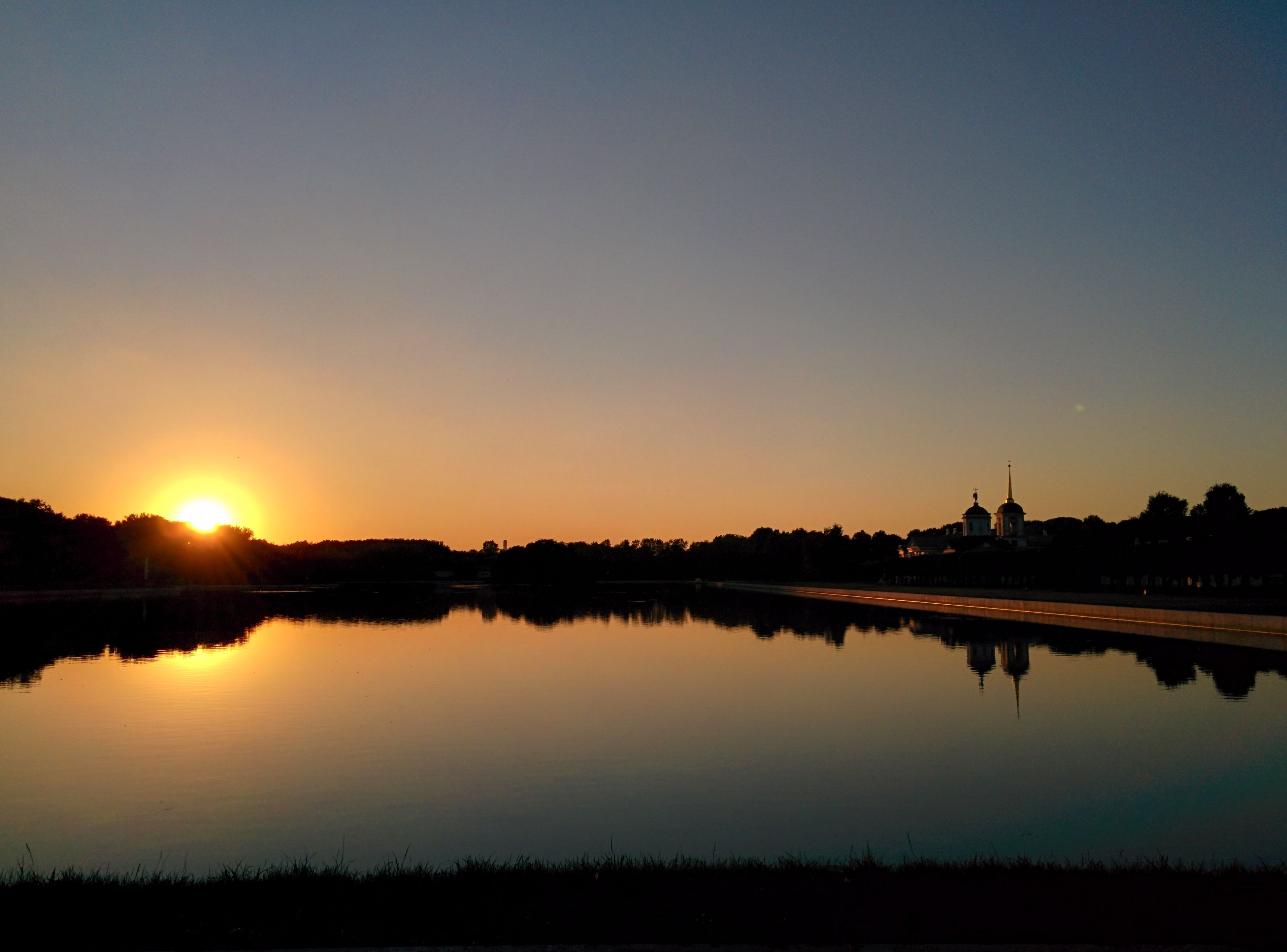 sunset, reflection, water, clear sky, silhouette, copy space, tranquil scene, lake, tranquility, scenics, sun, beauty in nature, standing water, nature, idyllic, river, orange color, calm, sunlight, landscape