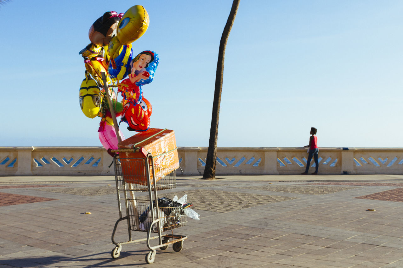 The balloon seller watches the sea on a few client days Balloons Balloons🎈 Clear Sky Day Multi Colored One Person Out Of Clients Outdoors Street Seller