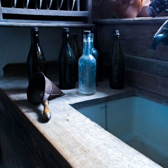 Glass bottles on an antique sink Bottles Close-up Day Empty Kitchen No People Shaker Sink Tap Wood - Material