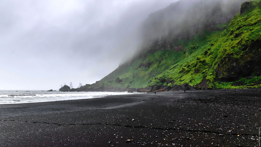 Plage de Vík í Mýrdal, un jour de pluie Beach Beauty In Nature Black Sand Beach Cliff Coastline Exploring Hill Iceland Iceland_collection Outdoors Physical Geography Power In Nature Rain Remote Rock Rock Formation Sand Scenics Sea Voyage Water