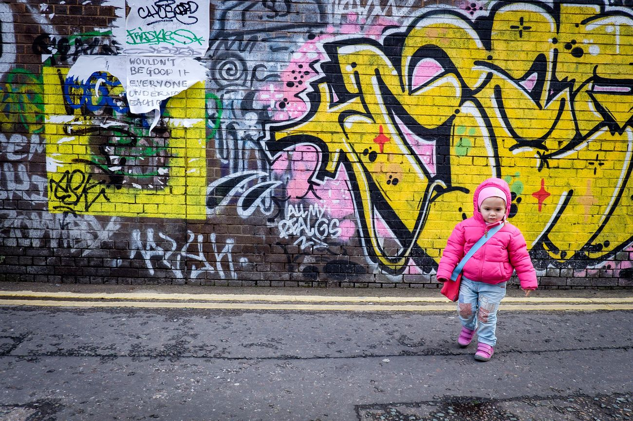 Millennial Pink Graffiti Full Length Wall - Building Feature Real People One Person Sidewalk Lifestyles Outdoors Front View Spray Paint Day People City Portrait Adult