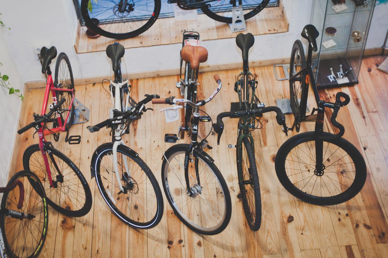 bicycle, mode of transport, transportation, land vehicle, stationary, bicycle rack, bicycle shop, cycling, parking, hanging, no people, racing bicycle, exercise bike, wheel, spoke, day, sport, indoors, tire, workshop, mountain bike