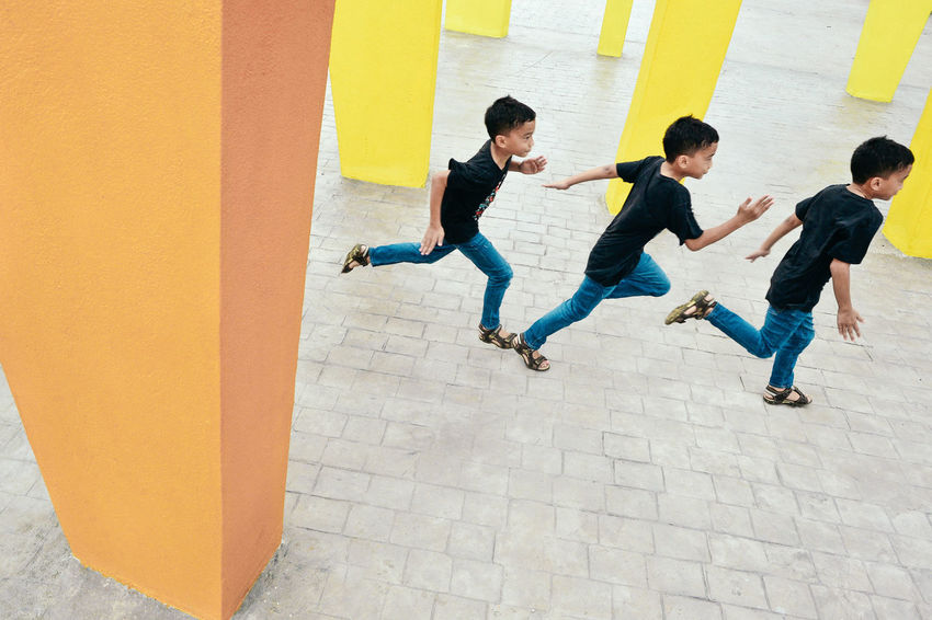 Multiple Exposures Boy Running Casual Clothing City Colorful Leisure Activity Lifestyles Motion Outdoors Playground Sequence Shot Togetherness Rethink Things