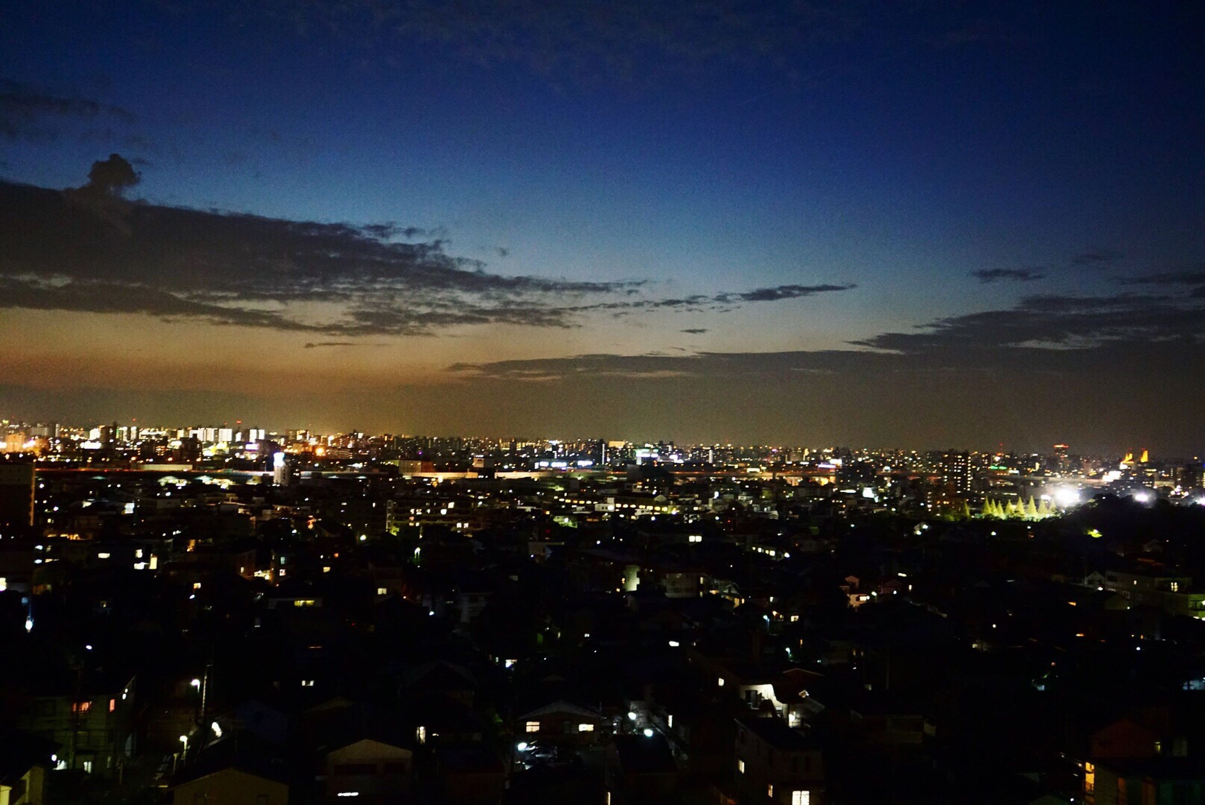 illuminated, city, architecture, cityscape, built structure, building exterior, night, sky, crowded, dusk, city life, high angle view, glowing, wide shot, wide, travel destinations, development, dark, cloud - sky, aerial view, modern, horizon, skyscraper, outdoors, residential district, majestic, no people, building story, scenics