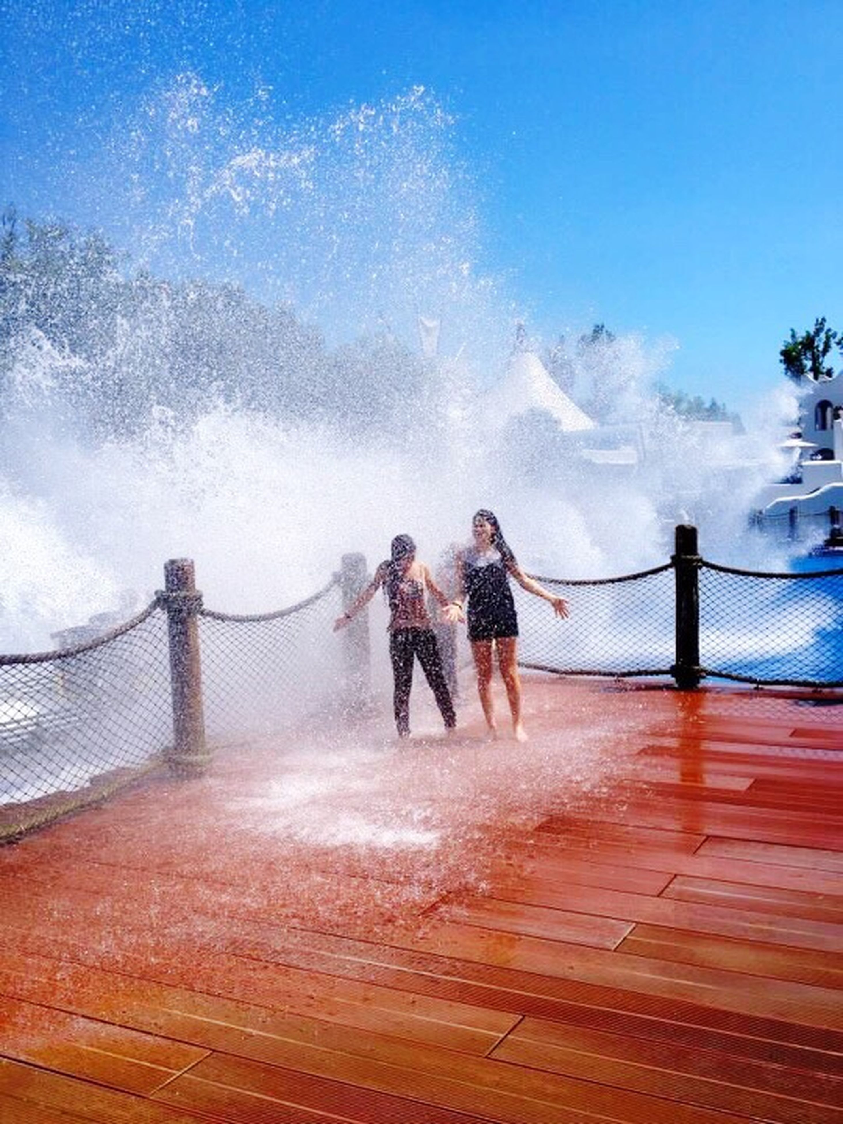 lifestyles, leisure activity, full length, men, water, railing, rear view, togetherness, sky, bonding, sea, walking, person, bridge - man made structure, standing, casual clothing, vacations, built structure