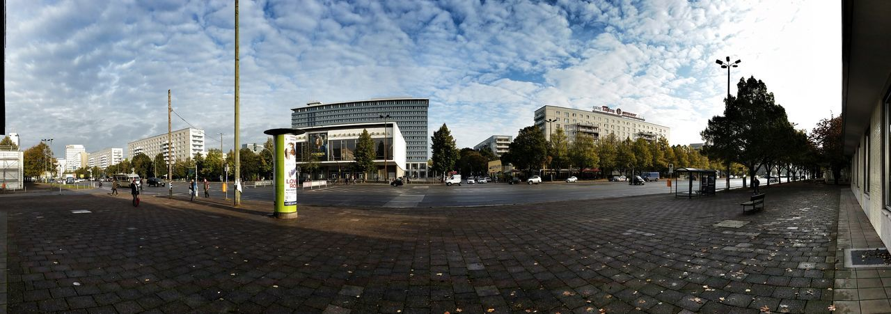 Panoramic View Of Buildings And Street In City Against Cloudy Sky