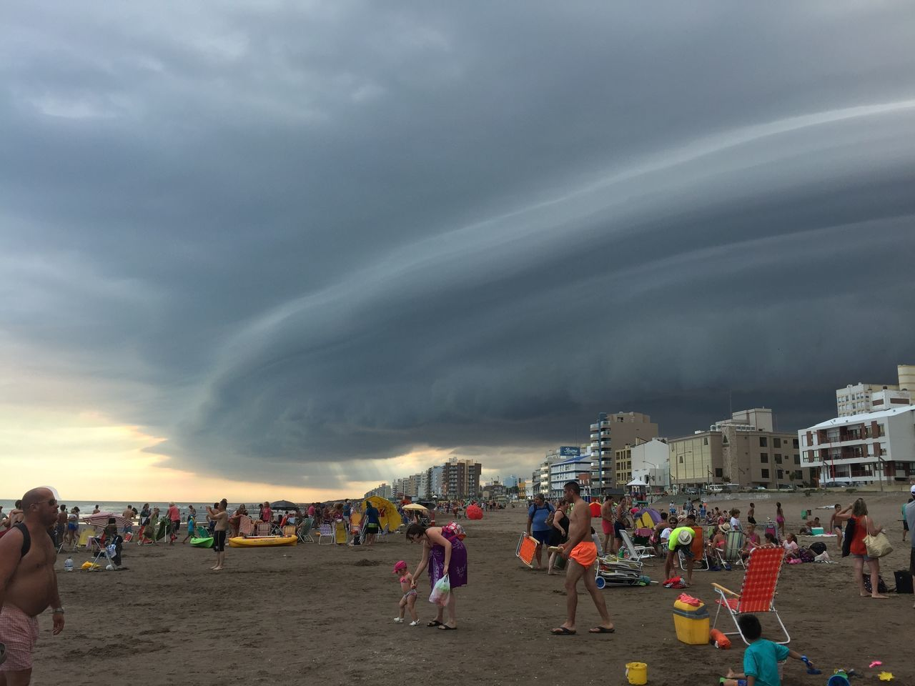 Crowd At Beach Against Cloudy Sky