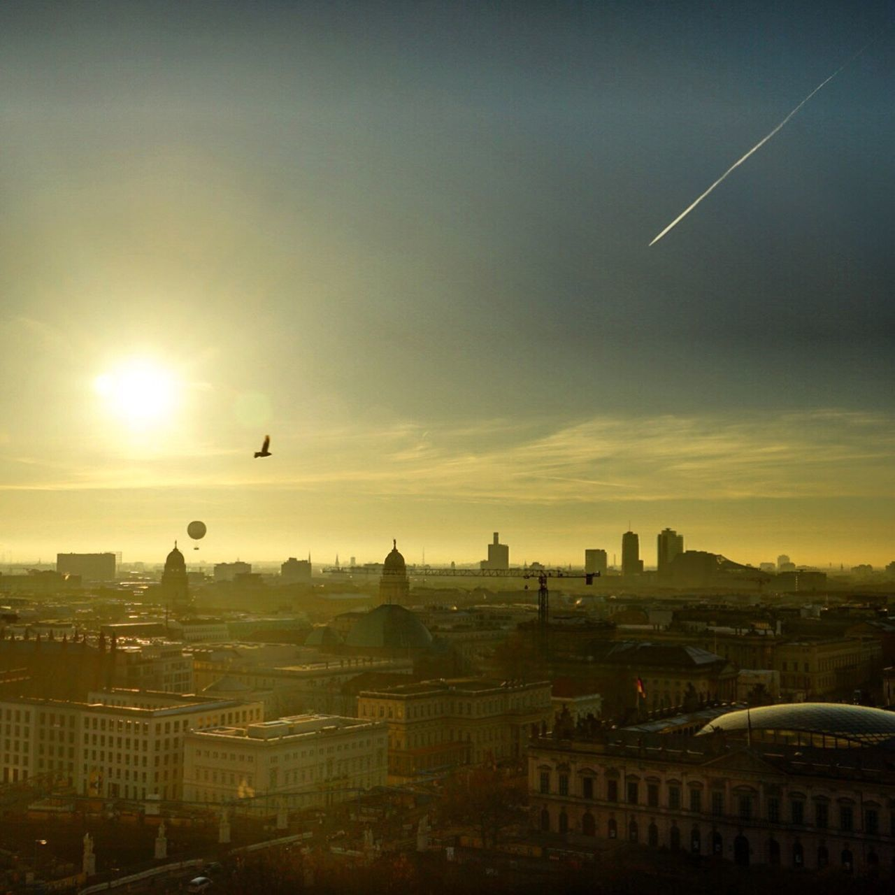 architecture, built structure, building exterior, flying, cityscape, sunset, city, sky, outdoors, no people, dome, vapor trail, nature, bird, day