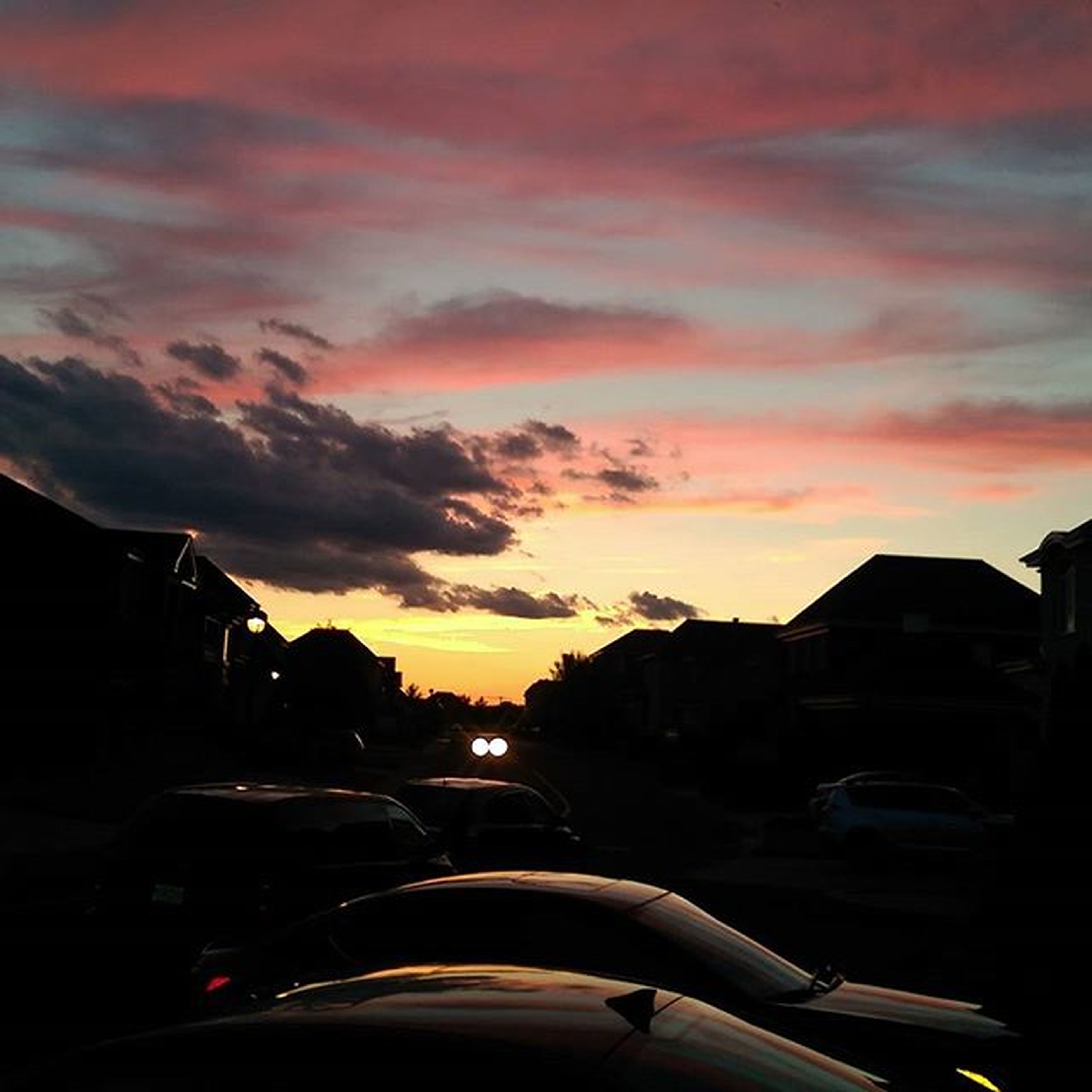 sunset, transportation, car, mode of transport, land vehicle, sky, orange color, cloud - sky, building exterior, architecture, road, built structure, street, silhouette, cloud, city, dramatic sky, cloudy, dusk, travel
